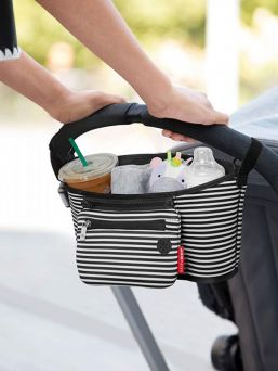 This insulated beverage and essentials caddy stretches to hold bottles and coffee cups securely, while providing easy access to your most important items. Includes a detachable wristlet for errands and a headphone port for hands-free calls.